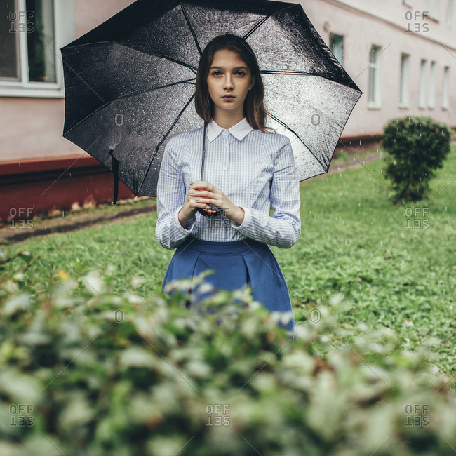 Portrait of teenager holding umbrella while standing on grassy field during rain