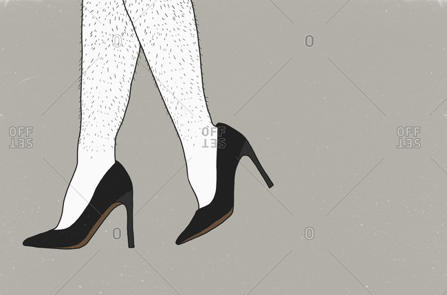 Low section of man wearing stilettos against gray background