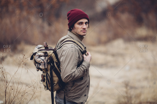 Portrait of man carrying backpack and standing in field