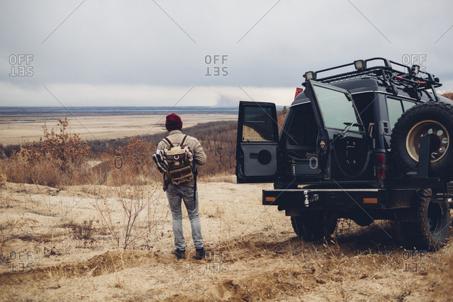 Rear view of hiker standing by sports utility vehicle on land against sky, Amur, Russia