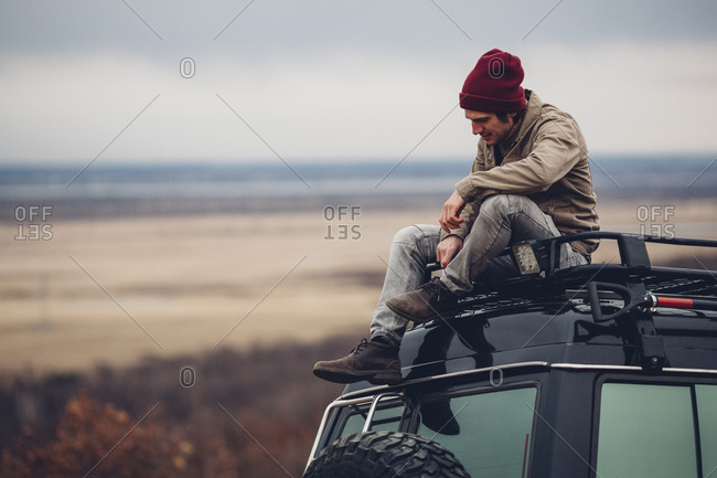 Man sitting on top of sports utility vehicle against landscape, Blagoveschensk, Amur, Russia