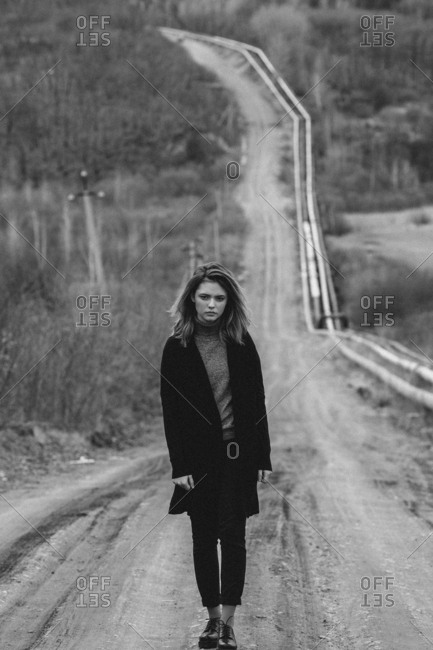 Full length of teenage girl standing on dirt road against trees