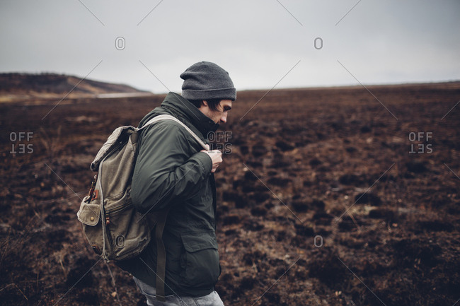 Side view of hiker carrying backpack while walking on barren landscape, Blagoveschensk, Amur, Russia