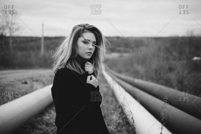Portrait of teenage girl standing amidst pipes on field against sky