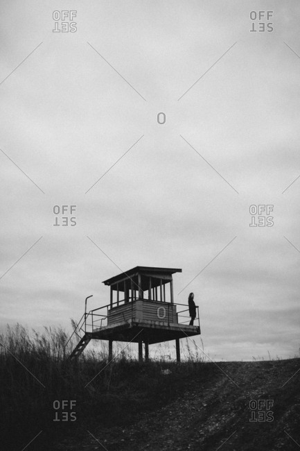 Distant view of teenager on lookout tower at field against sky