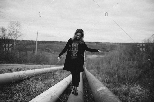 Full length of teenage girl walking on pipes over field against sky