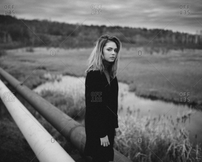Portrait of teenage girl standing amidst pipes by pond