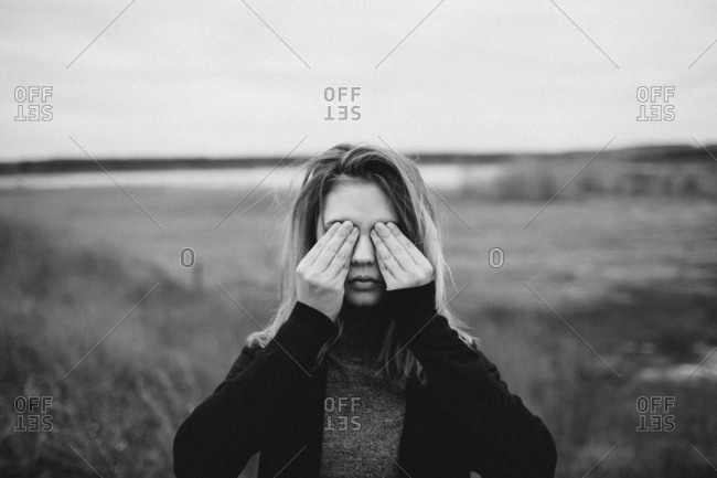 Teenage girl covering eyes while standing on field against sky