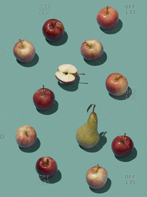 High angle view of pear amidst apples on blue background