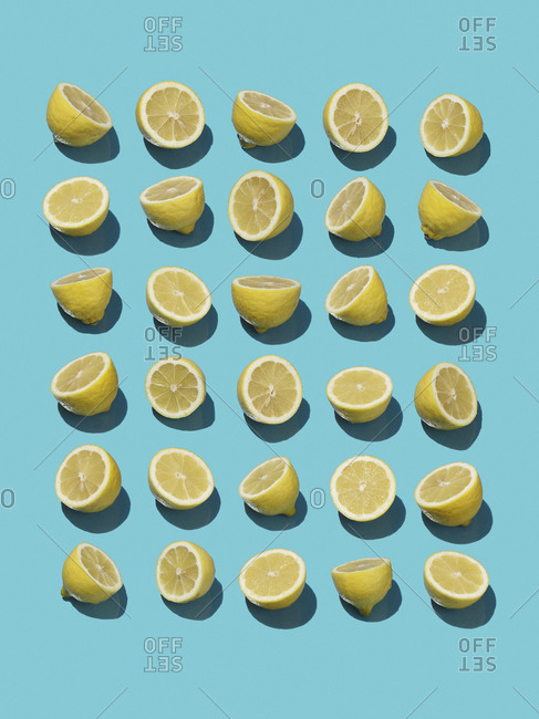 High angle view of sliced lemons on blue background