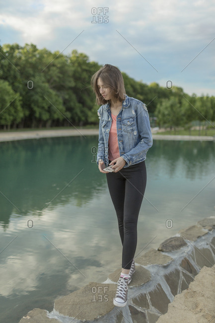 Full length of woman walking on retaining wall by lake at park