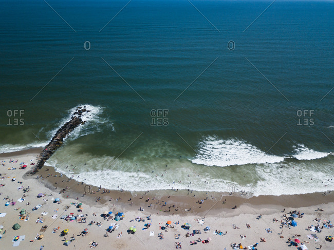 Beachgoers on a sandy beach near a jetty in the ocean