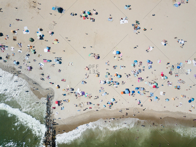 Umbrellas and beachgoers dotting a sandy beach