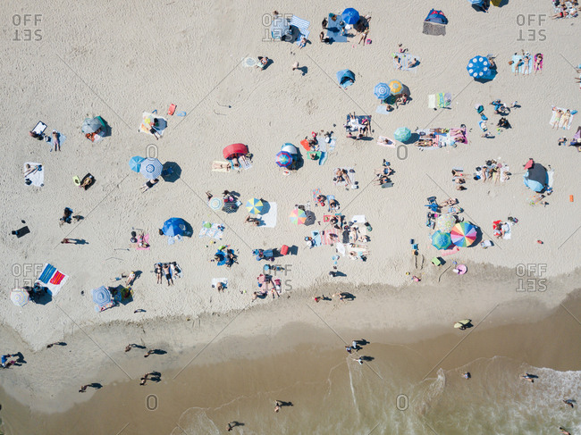 Beachgoers and colorful umbrellas on a beach near breaking waves