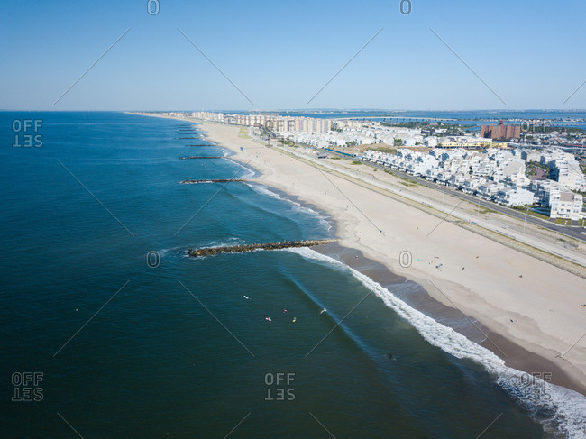 Aerial view of a vast beach and ocean dotted with surfers