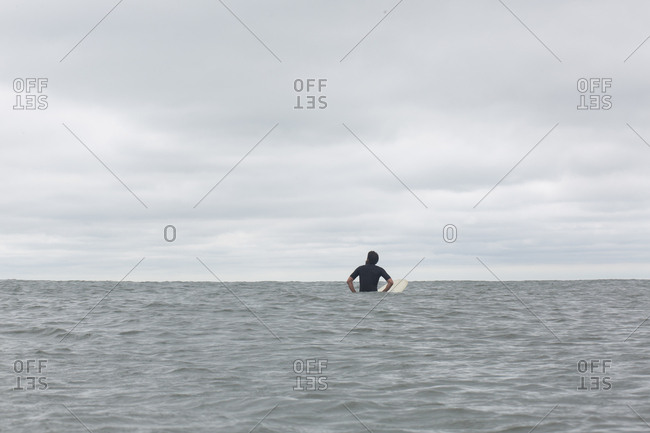 Surfer sitting on his board in the middle of an ocean