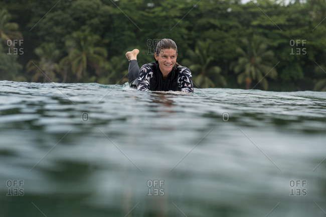 Woman paddling on surfboard in water at Bocas del Toro, Panama