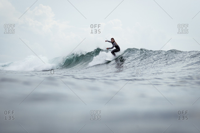 Woman surfing on wave on the coast of Panama