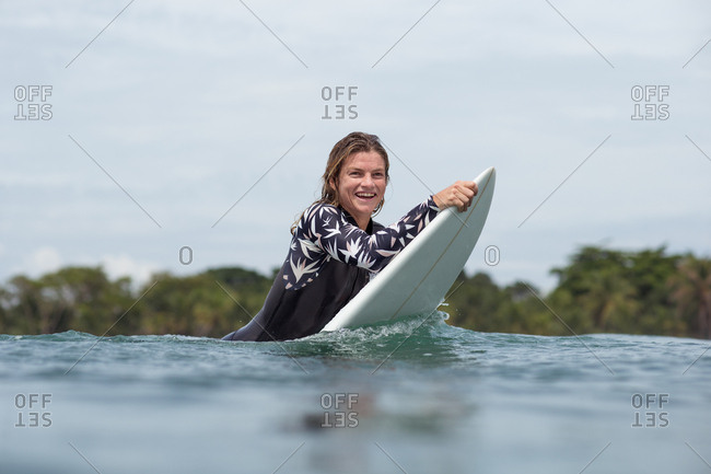 Smiling woman holding surfboard in the water on the tropical coast of Panama