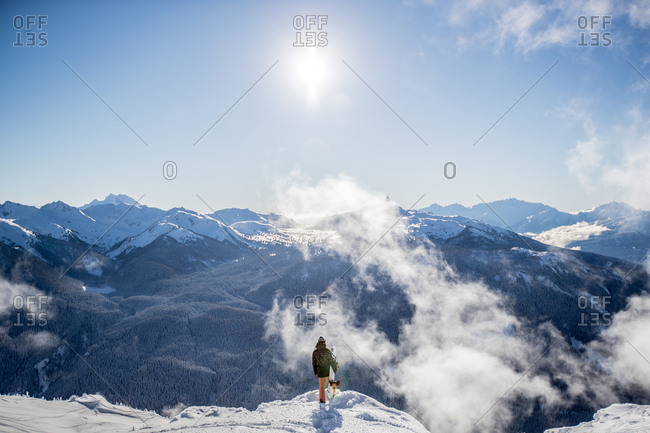 Person holding snowboard on snowy mountain summit looking out over scenic vista