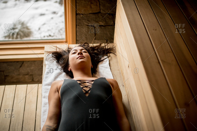 Woman lying down and relaxing in sauna
