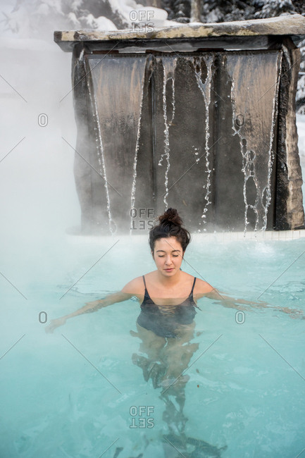 Woman relaxing in hot tub on winter day
