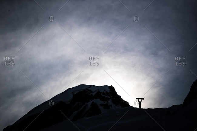 Silhouette of person holding snowboard above head near mountain summit