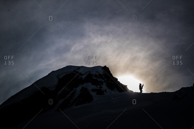 Silhouette of person holding snowboard near mountain summit