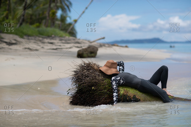 Woman lying with hat over her face on tropical island beach