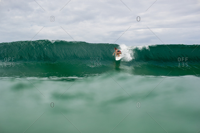 Woman surfing on wave on the coast of Bocas del Toro, Panama