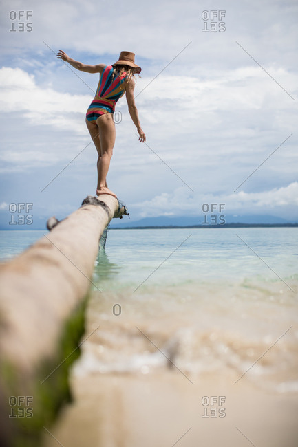 Woman balancing on palm tree log above water on sandy tropical beach