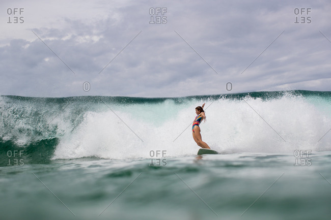 Woman balancing on surfboard while riding wave on the tropical coast of Panama