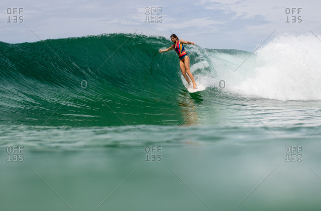 Woman on surfboard riding wave on the tropical coast of Panama