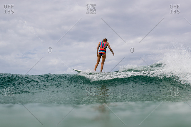 Woman balancing surfboard on wave on the coast of Panama