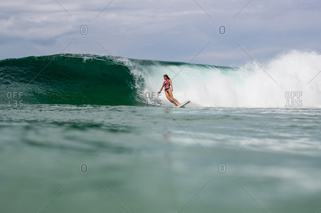 Woman surfing near wave on the tropical coast of Panama