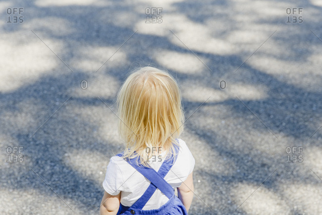 A blond toddler girl wearing a dark blue dress and white t-shirt seen from the back.