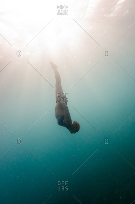 British Virgin Islands - March 15, 2017: A woman in a bikini and a swim cap and goggles dives into the water