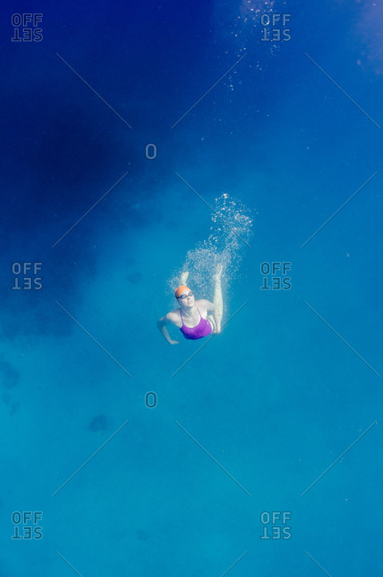 British Virgin Islands - May 13, 2015: A woman in a pink bathing suit and orange swim cap and goggles looks up from deep in the ocean