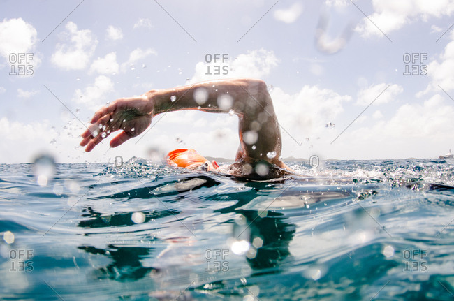 British Virgin Islands - March 17, 2017: A man in goggles and an orange swim cap takes a breath as he swims along the surface of the water
