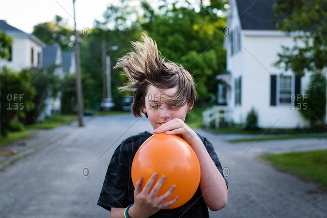 Bath, Maine, USA - May 13, 2015: A young boy lets the air out of an orange balloon