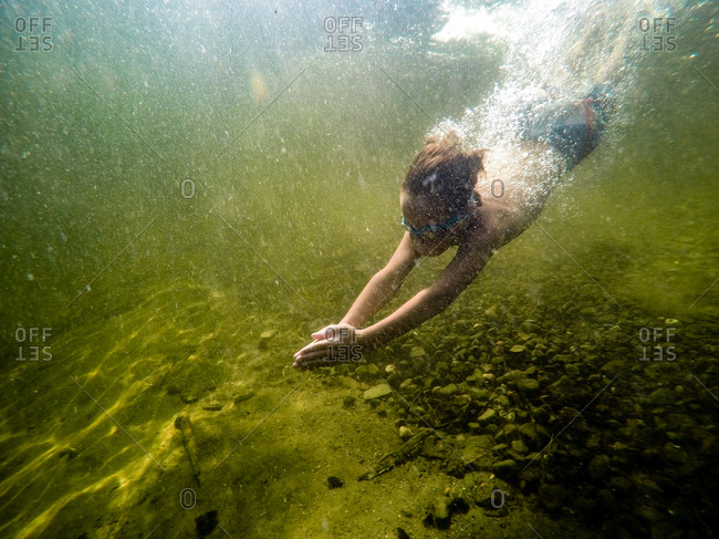 Moosehead Lake, Maine, USA - May 13, 2015: A young boy dives into a clear lake, wearing swim trunks and goggles, as seen from underwater