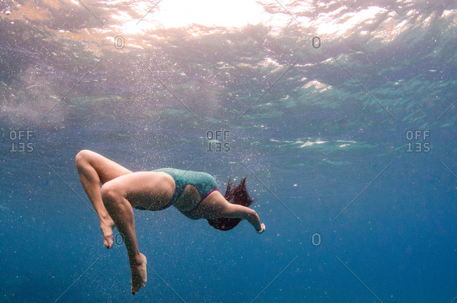 A woman in a green bathing suit does a back flip under water