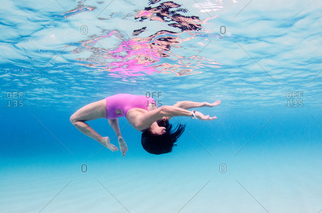 A woman in a pink bathing suit does a back flip in clear blue water