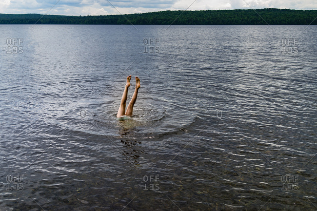 A teenage girl does a handstand in a pristine lake