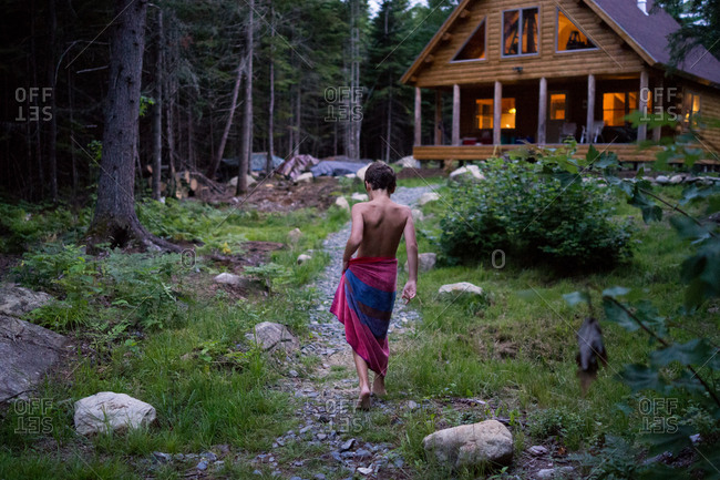 A young boy walks toward a log cabin with a beach towel around his waist