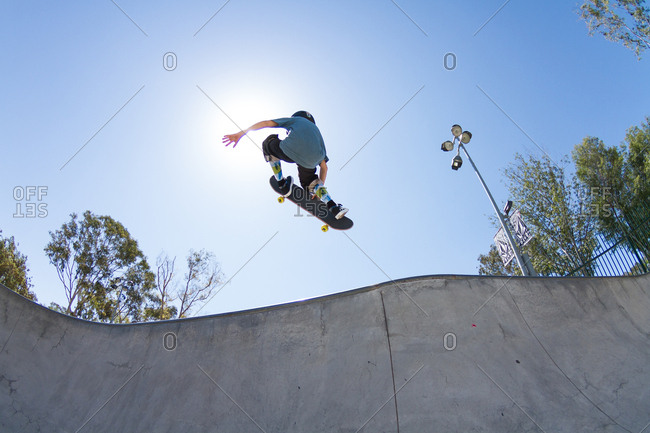 California, USA - August 17, 2014: Boy performs tricks at a skatepark