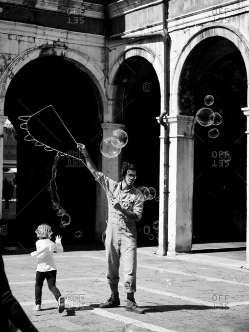 April 30, 2016 - Venice, Italy: Child playing with bubbles in square