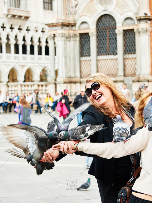 April 30, 2016 - Venice, Italy: People feeding pigeons in square
