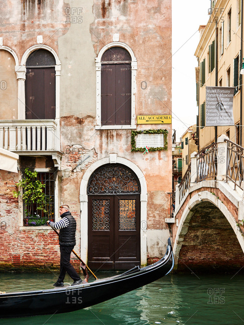 May 1, 2016 - Venice, Italy: Gondolier rowing past buildings
