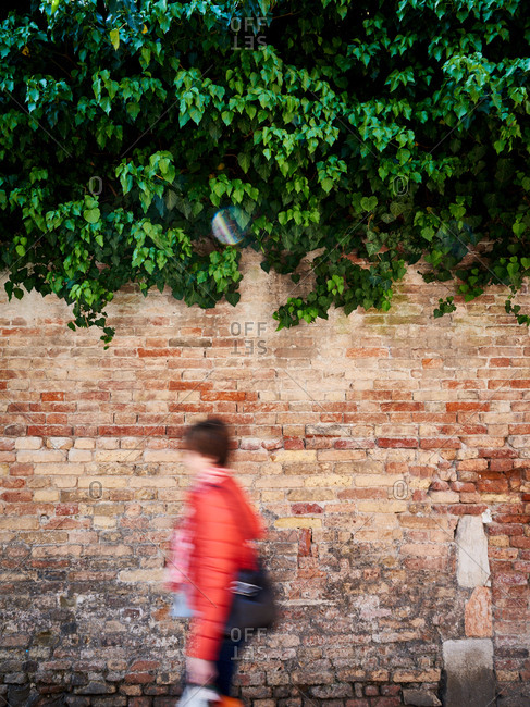 Blurred woman walking next to brick wall